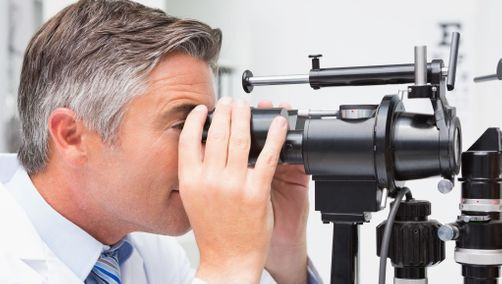 Optometrist looking in optical instrument in our Edmonton office