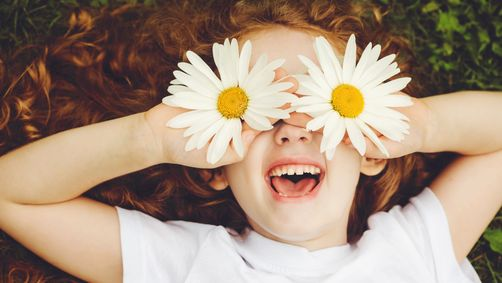 a young girl laughing and playing outside in the summer with daisies over her eyes